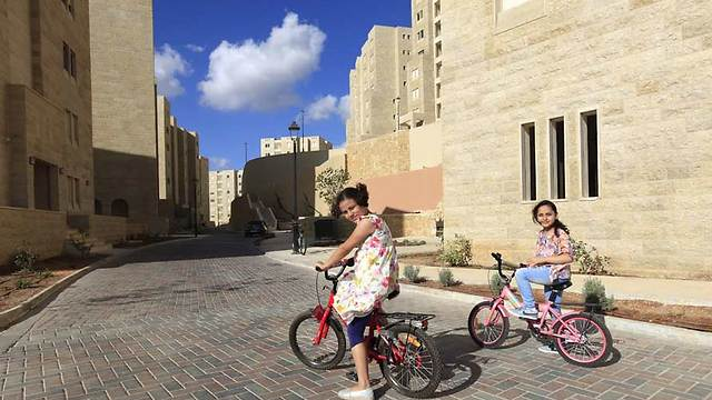 Bahee, 8, and Layan,10, bicycle in front of new apartment in Rawabi (Photo: Eloise Bollack/The Media Line)