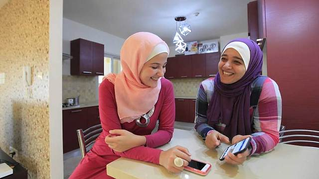 Hana and her daughter Tuqa in new apartment (Photo: Eloise Bollack/The Media Line)
