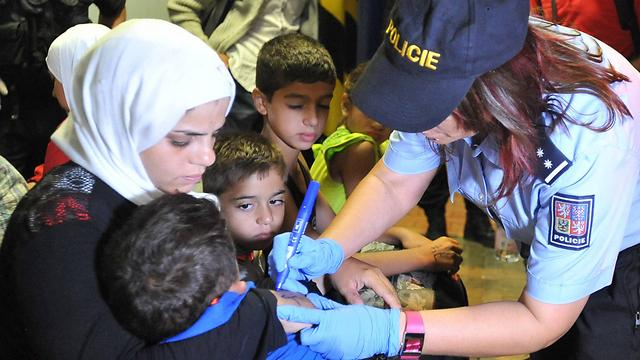 שוטרת צ'כית רושמת מספר על ידיים של פליטים שהגיעו מהונגריה ואוסטריה (צילום: AP) (צילום: AP)