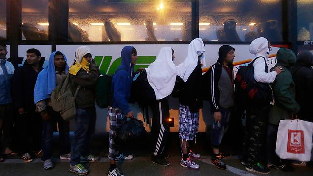 Boarding a bus going to the Austrian border (Photo: AP)