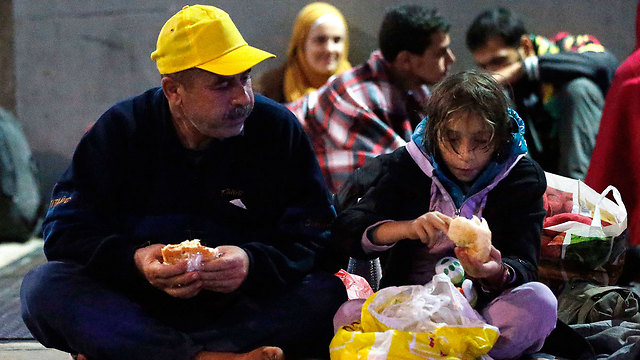 Exhausted migrants stop to eat at the Austrian border (Photo: AP)
