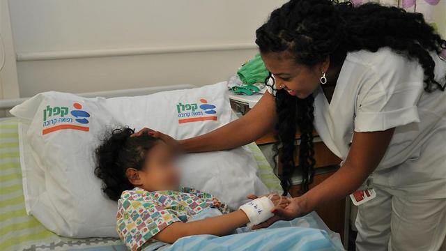 הילדה לאחר שהתאוששה, עם האחות דפי טגניה במחלקת ילדים (צילום: דוברות קפלן) (צילום: דוברות קפלן)