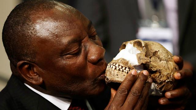 סגן נשיא דרום אפריקה מנשק את אחת הגולגולות שאותרו (צילום: AP)