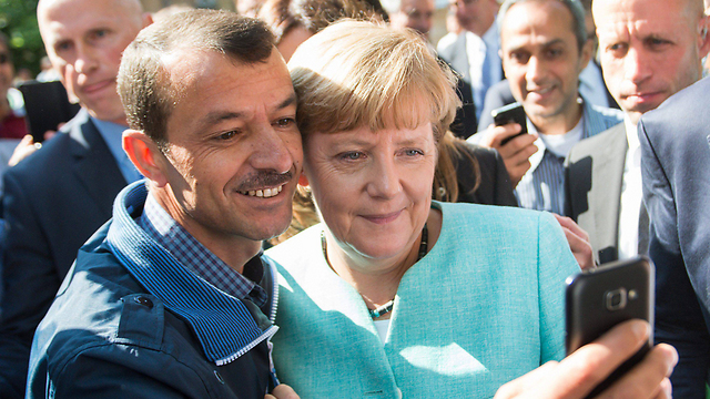 Angela Merkel has her picture taken with a refugee (Photo: EPA)