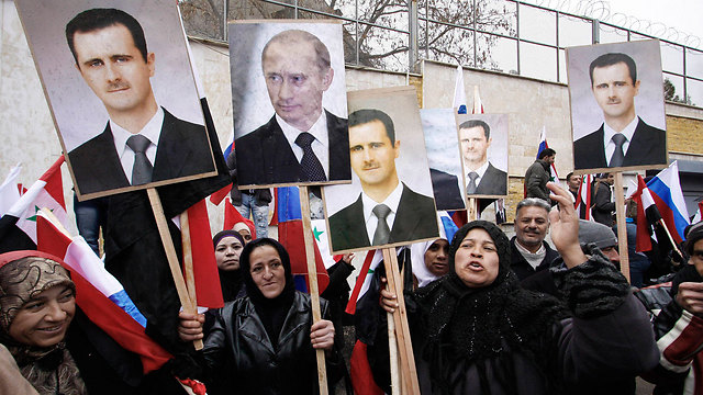 Syrians hold portraits of Assad and Putin (Photo: AP)
