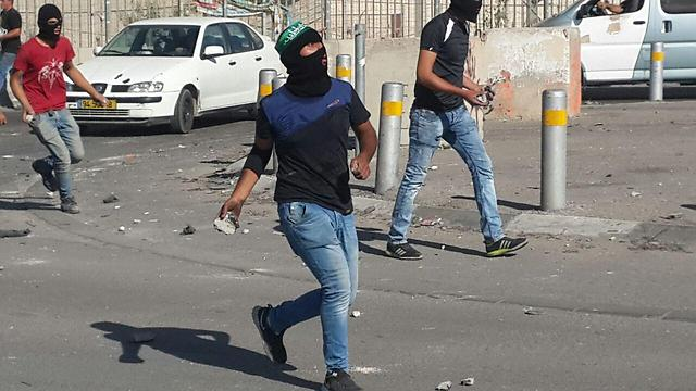Palestinian youth throw rocks in the Shuafat neighborhood of East Jerusalem Friday. (Photo: Hassan Shalaan)