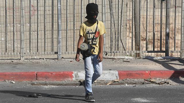 Masked boy with gas mask in Shuafat during disturbances this week (Photo: Gil Yohanan)