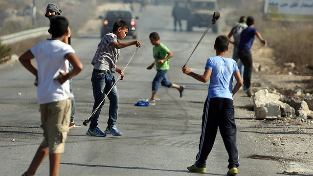 Palestinian youths throw stones at IDF forces (Photo: AFP)