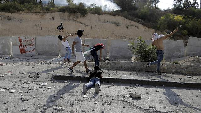 Palestinian youth throw rocks at security forces Sunday. (Photo: Reuters)