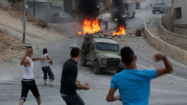 Palestinians throw rocks at military vehicles in Nablus. (Photo: AFP)