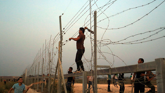 Gazans breaking through the Israel border fence (Photo: AFP)