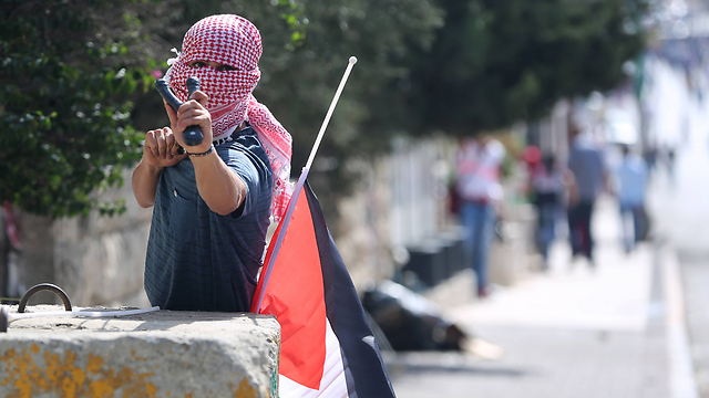 A Palestinian protester about to fire a slingshot towards IDF troops in Bethlehem (Photo: MCT)