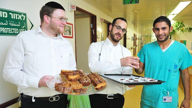 Subhi Koz, right, with two ultra-Orthodox men handing out cake (Photo: Rafi Kotz)