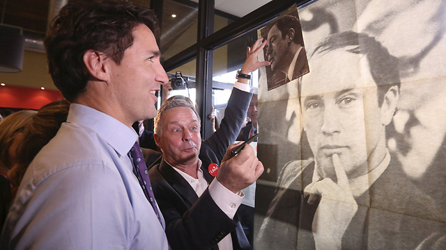 רוצה להמשיך את מורשת אביו. טרודו לצד תמונת ראש הממשלה לשעבר פייר טרודו (צילום: רויטרס) (צילום: רויטרס)