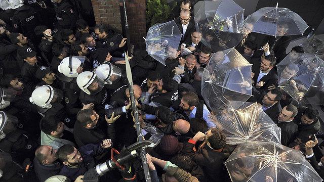 המפגינים הגנו על פניהם במטריות מפני גז הפלפל המשטרתי (צילום: AFP) (צילום: AFP)