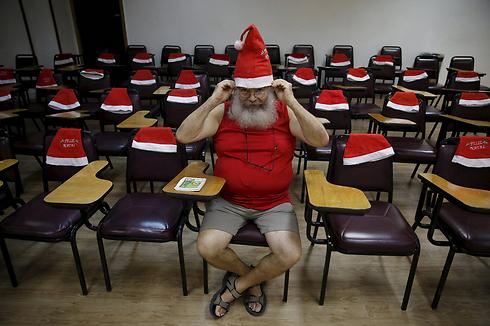 תלמיד חובש כובע לראשו לפני תחילת הלימודים בבית הספר לסנטה קלאוס בריו דה ז'ניירו, ברזיל. בית הספר מכשיר את תלמידיו למשימותיו השונות של סנטה קלאוס לקראת חג המולד. השיעורים כוללים שירה, פעילות גופנית, ולימוד כיצד להתלבש ואיך לעטות את הזקן הלבן המפורסם (צילום: רויטרס) (צילום: רויטרס)