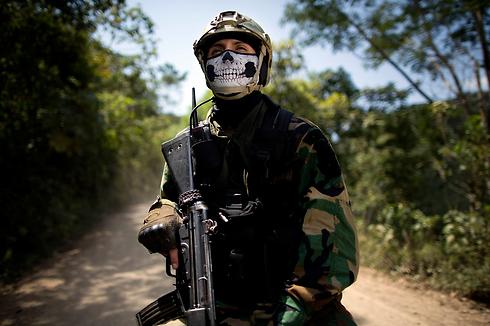 איש היחידה למלחמה בסמים של פרו שב לבסיסו לאחר מבצע להריסת מעבדה לא חוקית לייצור סמים בטינגו מריה (צילום: AP) (צילום: AP)