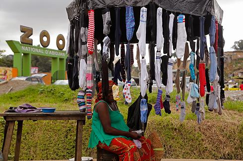 אישה מוכרת גרביים בכניסה לגן החיות בעיר אביג'ן, העיר הגדולה ביותר בחוף השנהב. הנשיא אלסאן אאוטרה זכה בניצחון סוחף בבחירות לנשיאות שנערכו בשקט יחסי לעומת הבחירות לפני חמש שנים (צילום: AP) (צילום: AP)