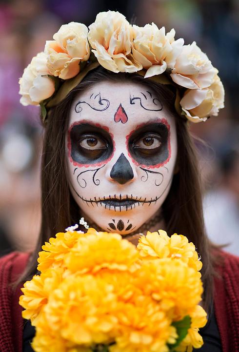 במכסיקו ציינו את יום המתים המוקדש לזכרם של אבות המשפחה שהלכו לעולמם. במהלך החג נוהגים ילדים לעטות מסיכה או לאפר את פניהם בציור גולגולת (צילום: AP) (צילום: AP)