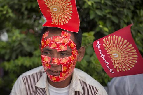 """תומך של """"מפלגת הפיתוח הלאומית"""" (NDP) עיטר את פניו בסטיקרים של המפלגה שמתמודדת בבחירות במיאנמר. הבחירות צפויות להיערך ב-8 בנובמבר והן הראשונות במדינה מאז שהשלטון עבר לידיים אזרחיות (צילום: AP) (צילום: AP)"""