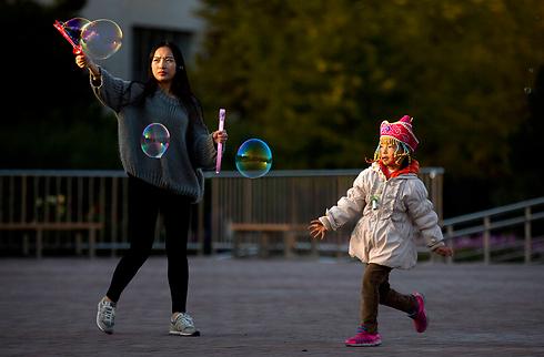 """אם ובתה משחקות בבועות סבון בפארק בבייג'ינג. המפלגה הקומוניסטית השלטת ביטלה באופן גורף את """"מדיניות הילד האחד"""", שבמסגרתה לכל זוג סיני הותר במשך עשרות שנים להביא רק ילד אחד לעולם (צילום: AP) (צילום: AP)"""