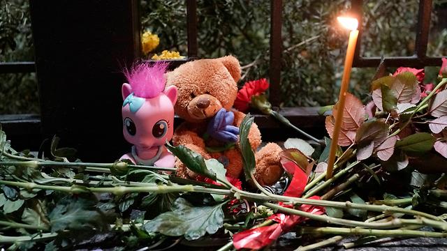 נרות ופרחים מול שגרירות רוסיה בקייב (צילום: AP) (צילום: AP)