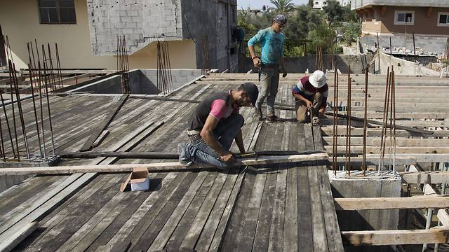 Palestinians work on rebuilding the house (Photo: Associated Press)