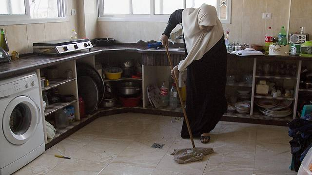 Um Alabed al-Zaza mops her new kitchen in the family's house (Photo: Associated Press)