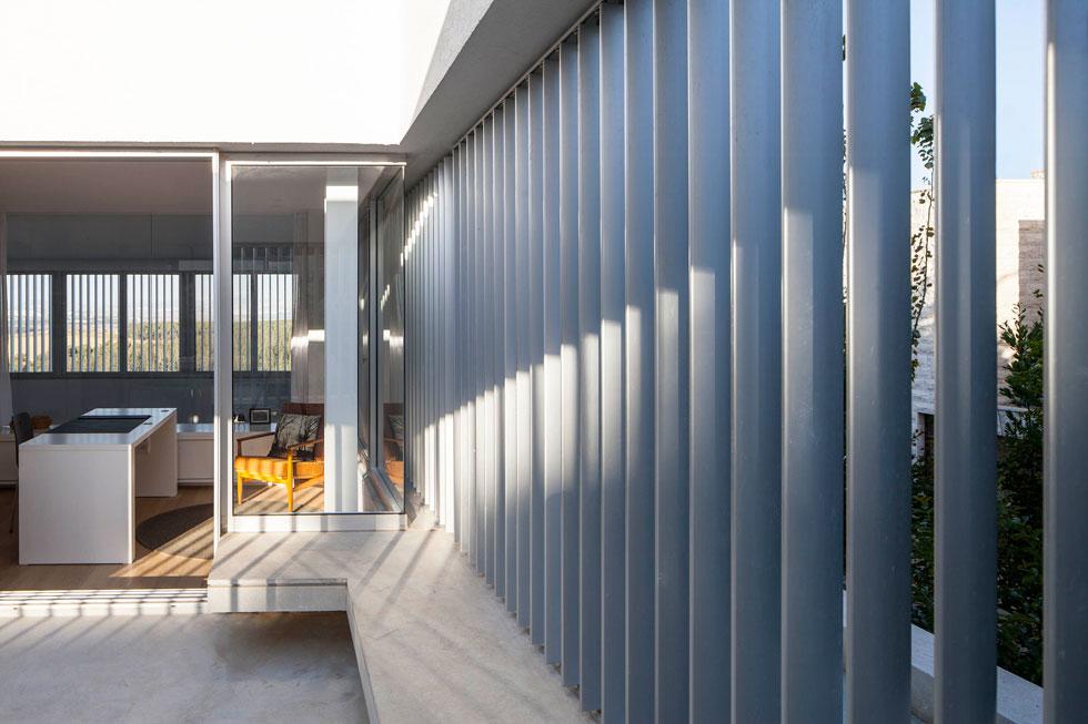 חדר העבודה שבקומה העליונה צמוד למרפסת גדולה, שמוקפת ברפפות אלומיניום אנכיות. הן מאפשרות כניסה של אור ואוויר, ובמקביל יוצרות תחושה של פרטיות (צילום: עמית גרון)