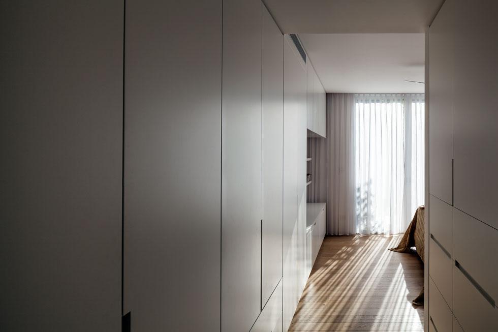 בחדר ההורים אווירה נינוחה, עם רצפת פרקט טבעי וקיר ארונות לבנים, שהופכים למדפים פתוחים בחלק שמול המיטה (צילום: עמית גרון)