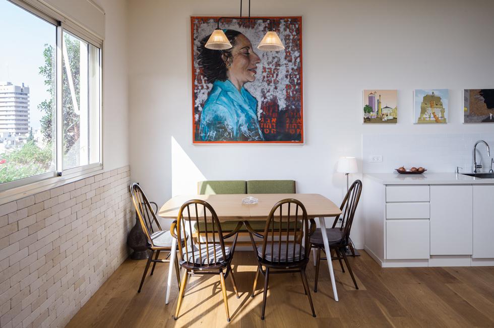 מעל פינת האוכל, כמו על קירות אחרים בבית, ציורים של דניאלה וכסלר, אמו של בעל הדירה. במטבח תלויה סדרת ציורים של האמן יזהר כהן (צילום: טל ניסים )
