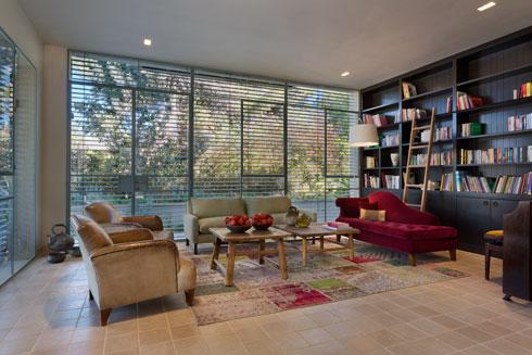 הסלון תחום בין 3 קירות - שניים מזכוכית ואחד שהוקדש לספרייה (צילום: אסף פינצ'וק)