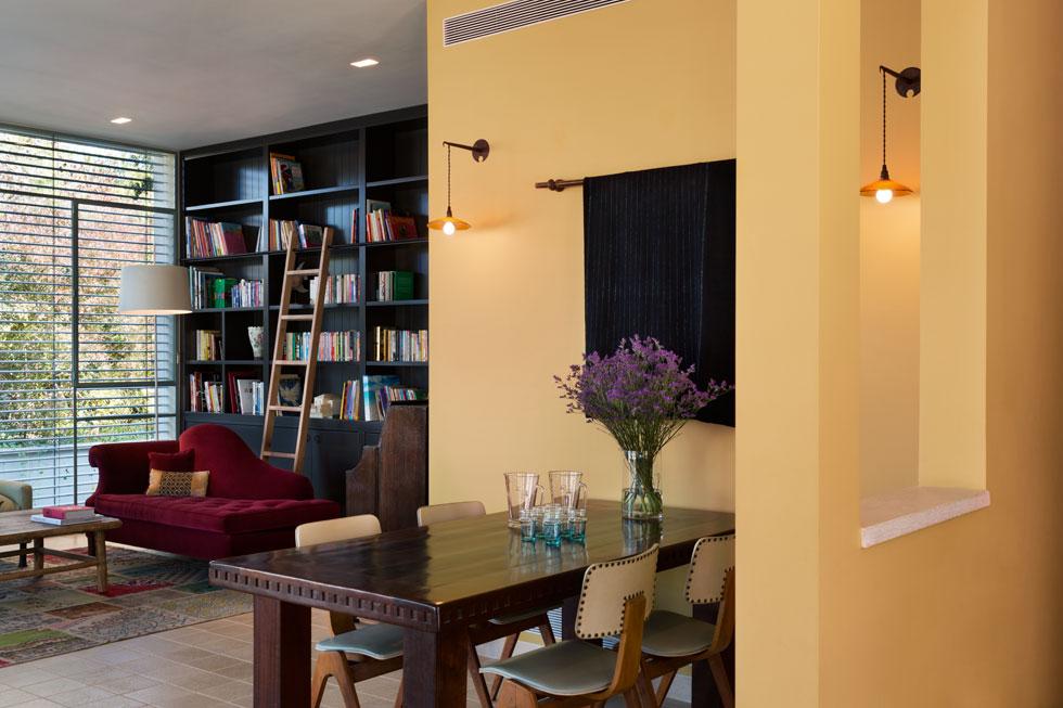 """שטח הבית הוא 390 מ""""ר. בתמונה: הסלון ופינת האוכל, שכוללת שולחן עץ כהה וכיסאות וינטג' משוק הפשפשים. הבד שתלוי לצדה הוא עבודת יד ממרוקו (צילום: אסף פינצ'וק)"""