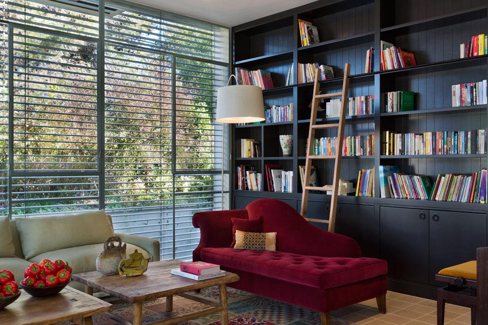 שתי הספות בסלון הובאו מפריז. הצבעים כהים, אך ליד הספרייה ניצבת מנורה לבנה מדגם Twiggy floor lamp, שנרכשה ב-CONRAN (צילום: אסף פינצ'וק)