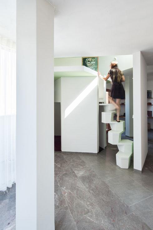 """ד""""ר זימרמן עולה לקומת הגלריה. ספק סולם, ספק מדרגות (צילום: טל ניסים)"""