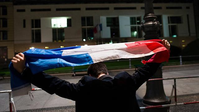 אדם עם דגל צרפת מול השגרירות בגרמניה (צילום: EPA) (צילום: EPA)