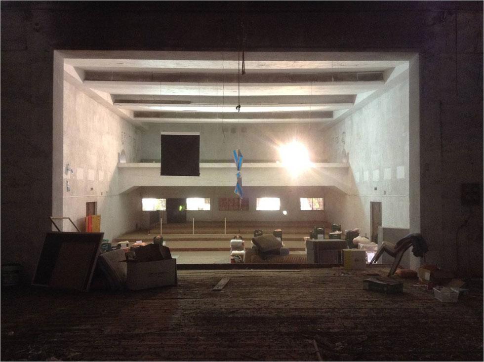 מבט מהבמה לכיוון האולם והיציע. תחת רצפת העץ תוכנן מקלט ששימש כסליק נשק ומטווח לאימוני ירי של אנשי ההגנה וכמחסן לאפסון דלק מטוסים (באדיבות סטודיו 826)
