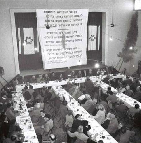 """שמואל דיין נושא דברים בכנס של ארגון """"החורש"""", 1957 (באדיבות ארכיון מושב נהלל)"""