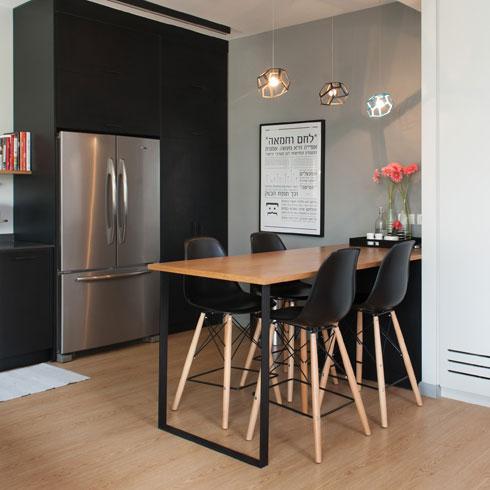 את הקיר ליד שולחן האוכל הגבוה מעטרת תמונה מפרויקט הגמר של בעל הבית, מעצב גרפי בוגר בצלאל (צילום: גלית דויטש)