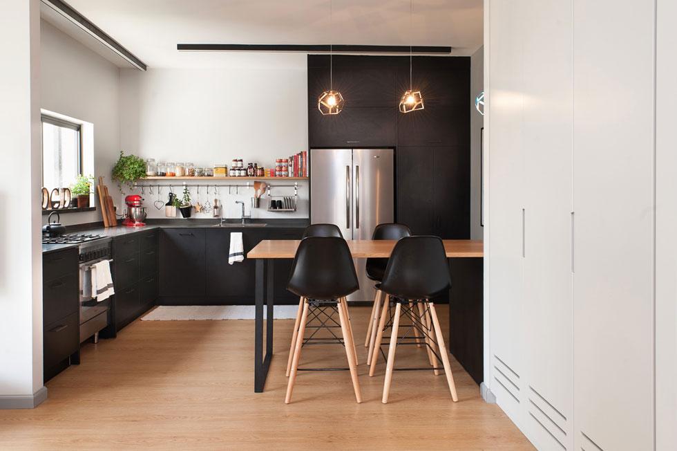 המטבח תופס את מקומה של מרפאת השיניים של בעל הדירה הקודם. ארון קיר גדול ולבן מסתיר את מערכות החשמל והתקשורת ואת כלי הניקוי. כדי לשמור על מסגרת התקציב נבחרו ארונות מטבח מפורמייקה שחורה. שולחן האוכל גבוה, ויכול לשמש כמשטח עבודה נוסף (צילום: גלית דויטש)