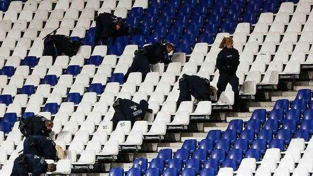 השוטרים הגרמנים מחפשים אחר החפץ החשוד באצטדיון בהאנובר (צילום: AP) (צילום: AP)