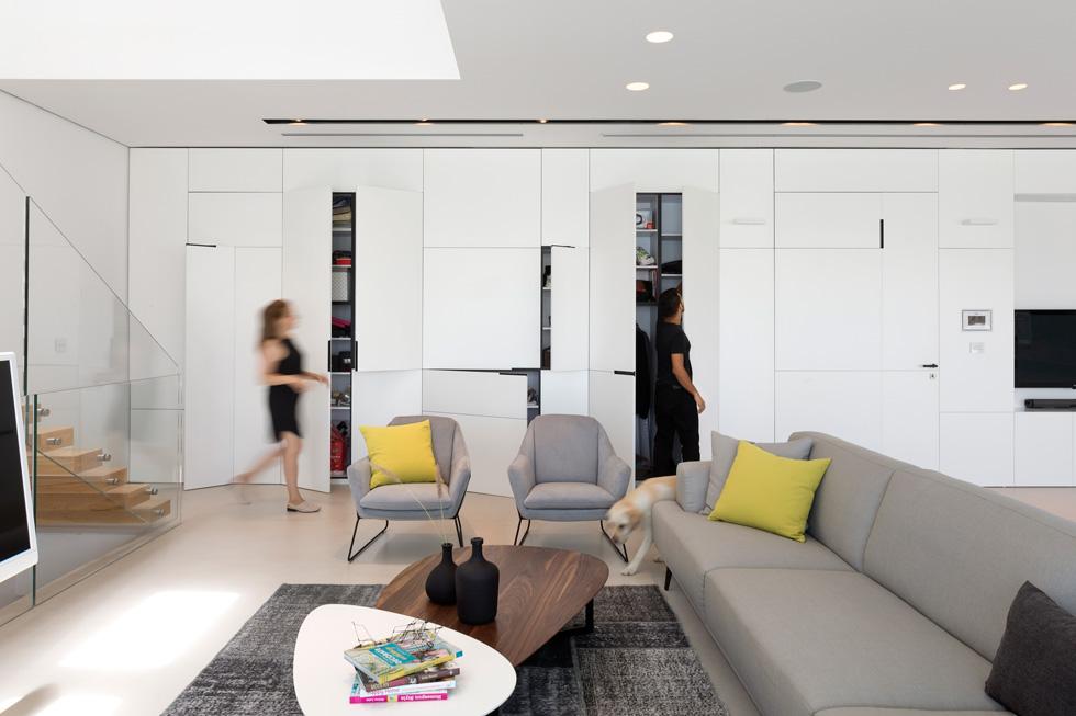 בקיר העץ הלבן משתלבים גם מסך הטלוויזיה ודלתות שמסתירות ארונות לאחסון ולמערכות החשמל והמיזוג (צילום: שי אפשטיין)