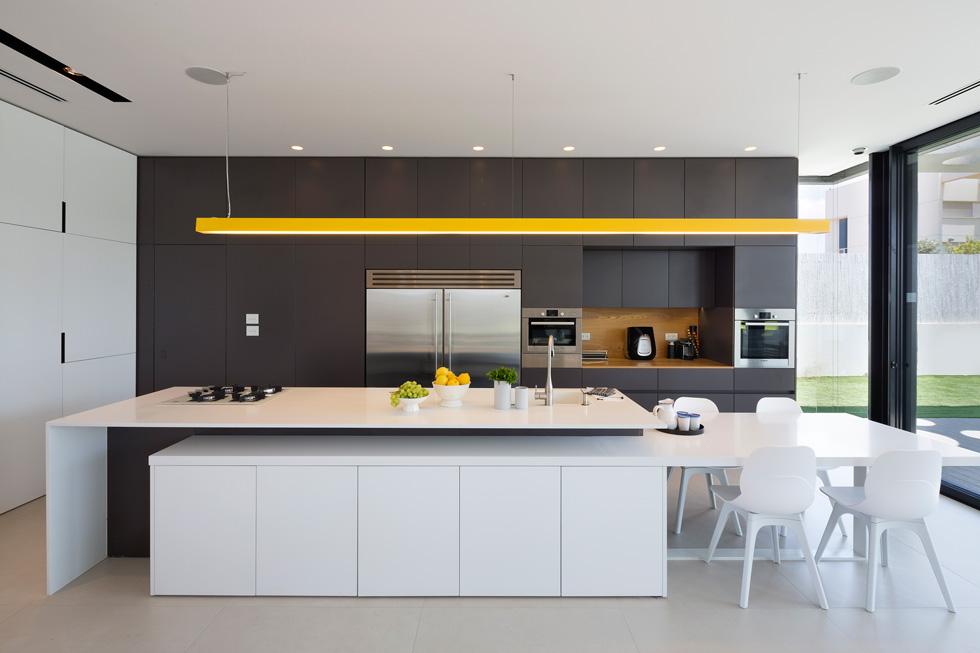 המטבח בנוי בשני קווים מקבילים: אי שעליו מבשלים (עם הפנים לסלון), וקיר ארונות אפורים שמגיעים עד התקרה. מצד ימין ניתן לראות מרווח מוקף חלונות זכוכית, שהאדריכלים השאירו כדי ליצור תחושה של פתיחות ועומק. בקיר הארונות מסתתרת גם הדלת לשירותי האורחים (צילום: שי אפשטיין)