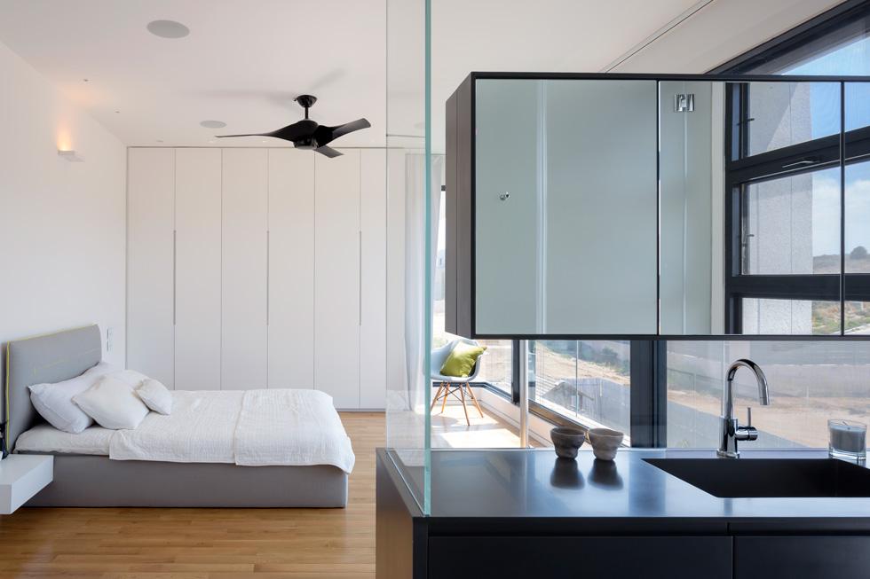 חדר ההורים נמצא מעל הבריכה וגם לו קיר של חלונות זכוכית, עם וילון חשמלי. ארון רחצה ומראה מפרידים בין אזור המיטה למקלחת ולשירותים הצמודים (צילום: שי אפשטיין)