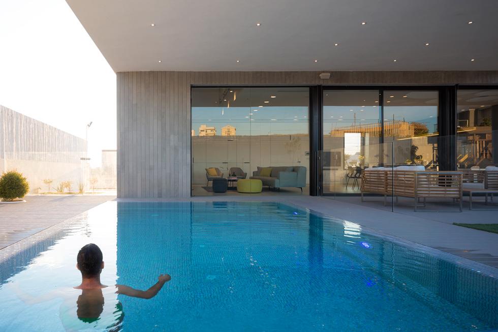 הבריכה שמאחורי הבית. בחלונות הגדולים אפשר לראות את השתקפות הנוף והבנייה סביב: 450 בתים צמודי קרקע חדשים (צילום: שי אפשטיין)