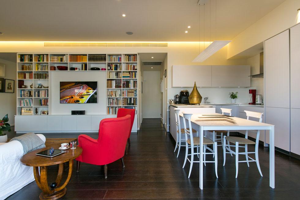 הריהוט שהובא ממילאנו מתבסס על עבודות עץ בסגנון בידרמאייר. שתי כורסאות אדומות שופכות כתמי צבע על החדר הלבן (צילום: שירן כרמל)