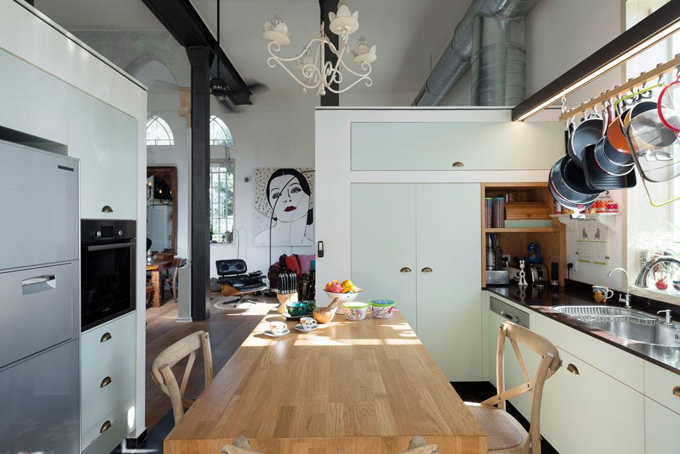 המטבח סגור חלקית, עם קירות שלא מגיעים לתקרה. ארונות בצבע טורקיז בהיר נבנו בתוך נישות גבס שמקיפות אי מעץ (צילום: גדעון לוין )