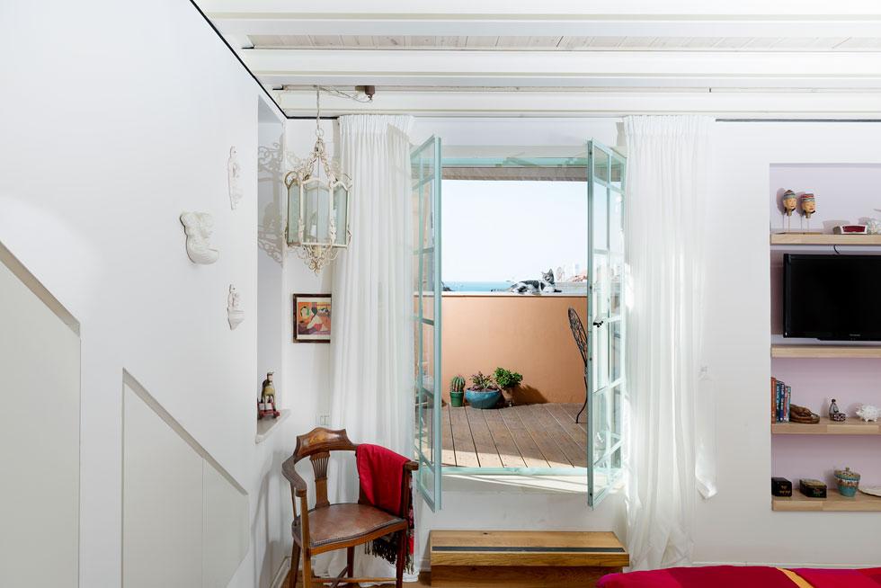 מחדר השינה יש יציאה למרפסת שמלווה את כל הקומה לאורכה, ושממנה יש נוף לים. החלונות והדלתות מוסגרו בטורקיז גם הם, בהשראת ביקור בתוניס (צילום: גדעון לוין )