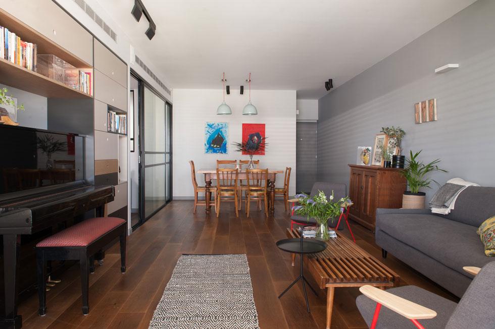 החלל הציבורי בדירה מלבני וגדול. הסלון עוצב בגוני אפור ועץ, עם שתי כורסאות פוליגון ושולחן עץ משנות ה-40. פינת הישיבה פונה אל ספרייה, שבמרכזה ניצב הפסנתר (צילום: גלית דויטש)