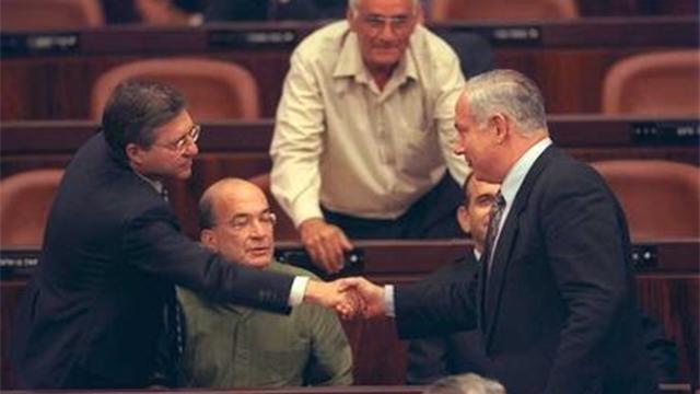 """1999: ממשלה הולכת. נתניהו מפנה את כסאו לממשלת ברק ולוחץ יד ליוסי ביילין. ברקע, יוסי שריד וח""""כ חיים אורון  (צילום: אבי אוחיון, לע""""מ) (צילום: אבי אוחיון, לע"""